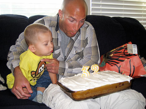 Eric and son blowing out candles on 32 birthday