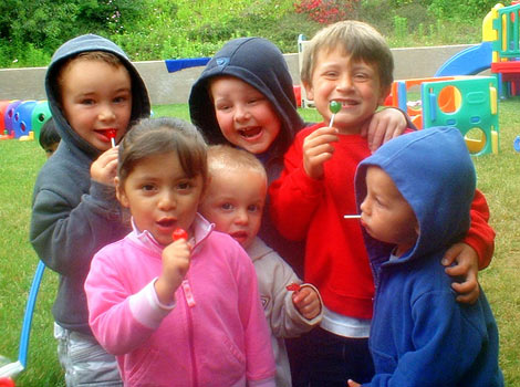children playing outside and sucking on lollipops