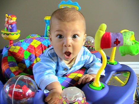 adorable baby is exersaucer with surprised face