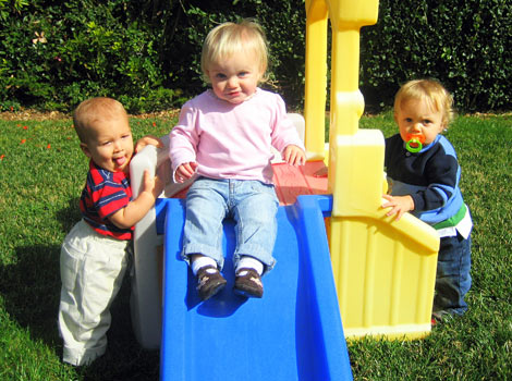 3 babies playing on small slide