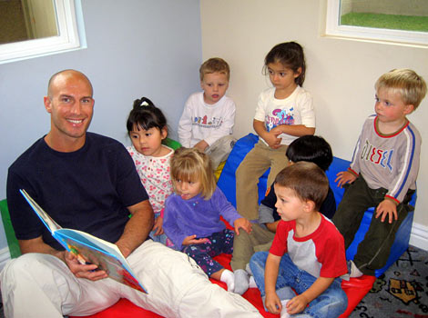 male child care provider reading at Building Blocks Home Daycare