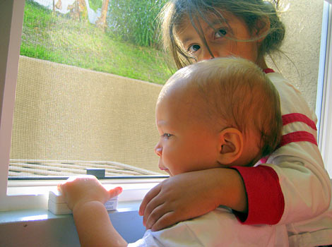 older and younger child looking out window