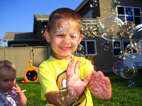 children popping bubbles outside