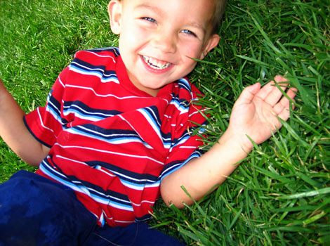 boy laughing hard in the grass